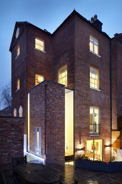 At night, the house's unique windows glow brightly, much like a lantern. Photo 9 of Lantern Home modern home