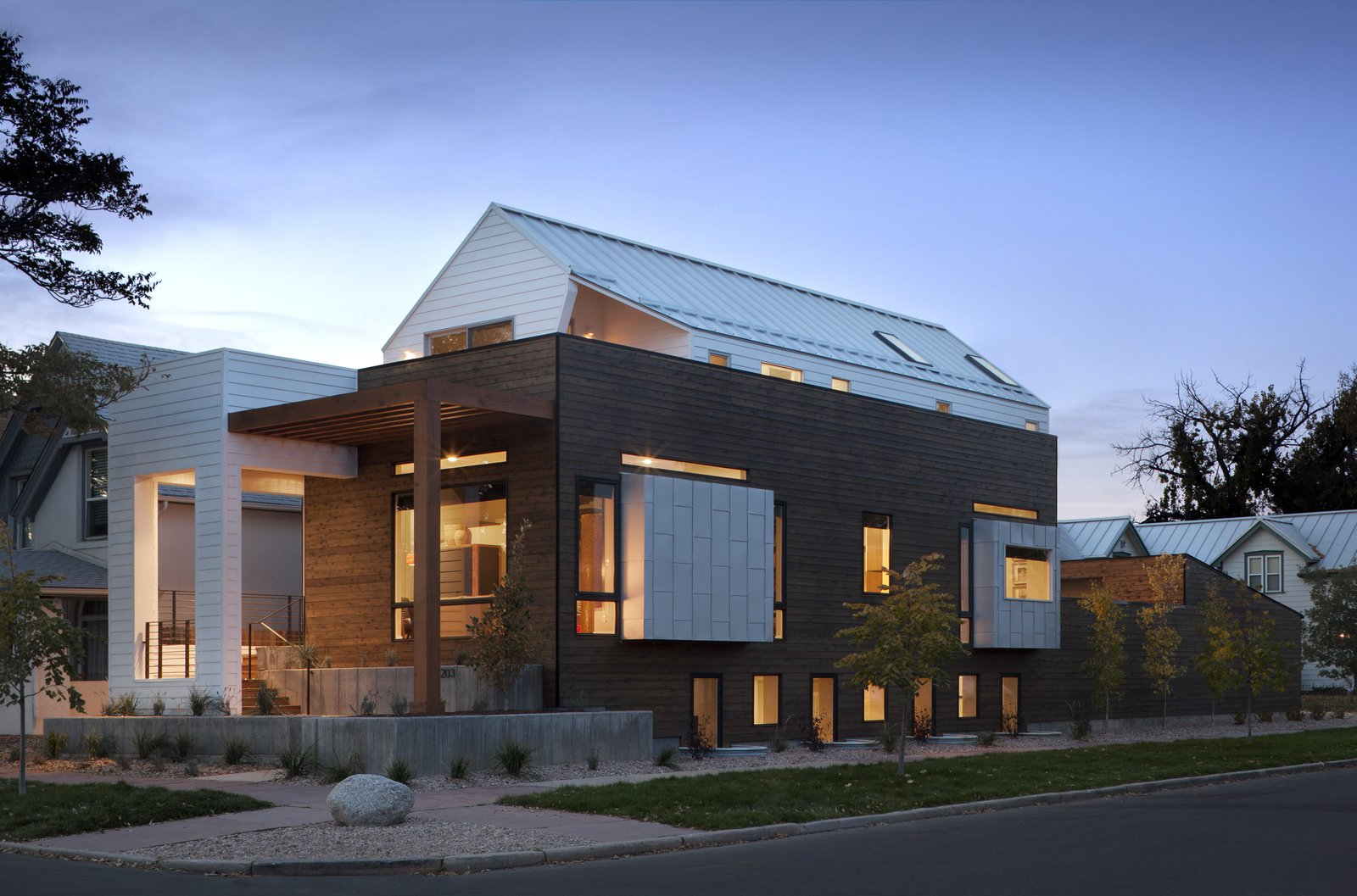 "Apart from a ""generous"" master bedroom, Mitchell says that the couple also wanted a rooftop deck to see views of downtown Denver. A sloped roof kept the building up to code, and the outdoor deck ""was achieved by shifting the upper volume backwards from the front of the house,"" he says. Tagged: Exterior, Wood Siding Material, Metal Siding Material, and Gable RoofLine.  Modern Homes in Colorado by Luke Hopping from Mile High Design: 5 Modern Homes in Denver"