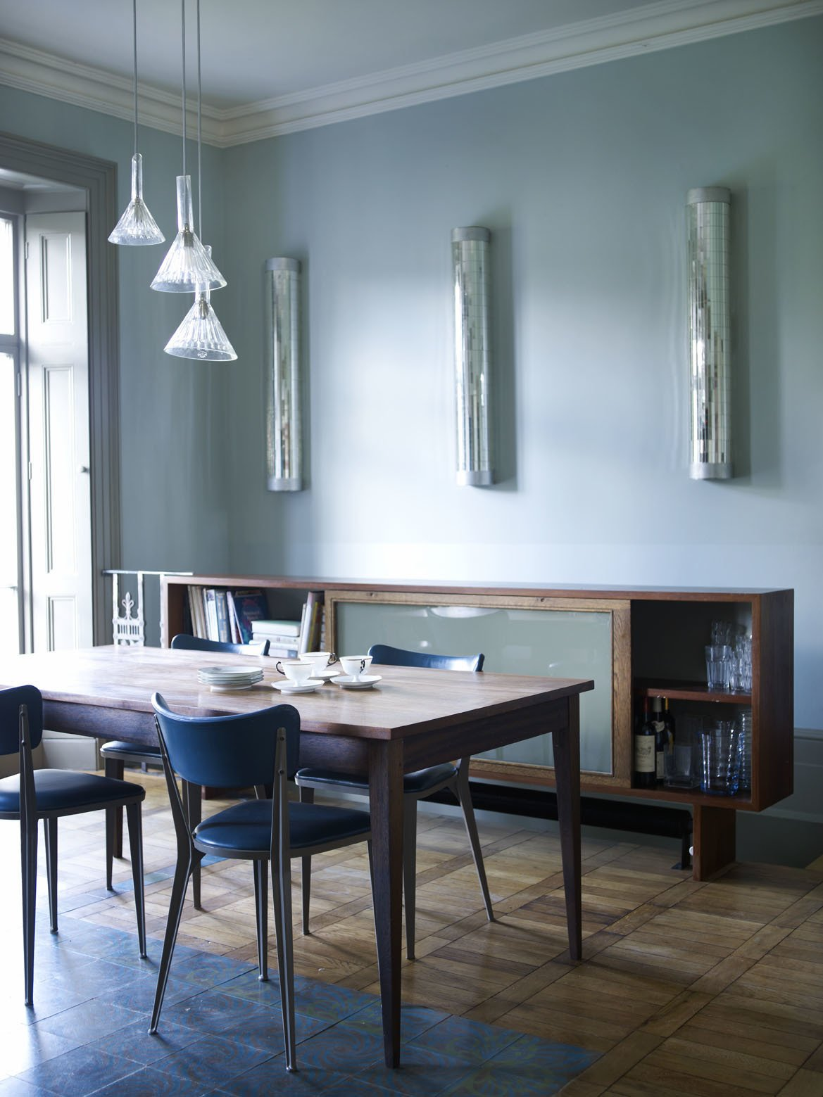 """The center of the dining room is marked out by a """"carpet"""" of terracotta, turquoise and green cement tiles from Emery & Cie. They are a practical, hard-wearing floor surface for a high-traffic area.  Photo 1 of 12 in A Gracious London Terrace House Is Reborn with Salvaged Materials"""