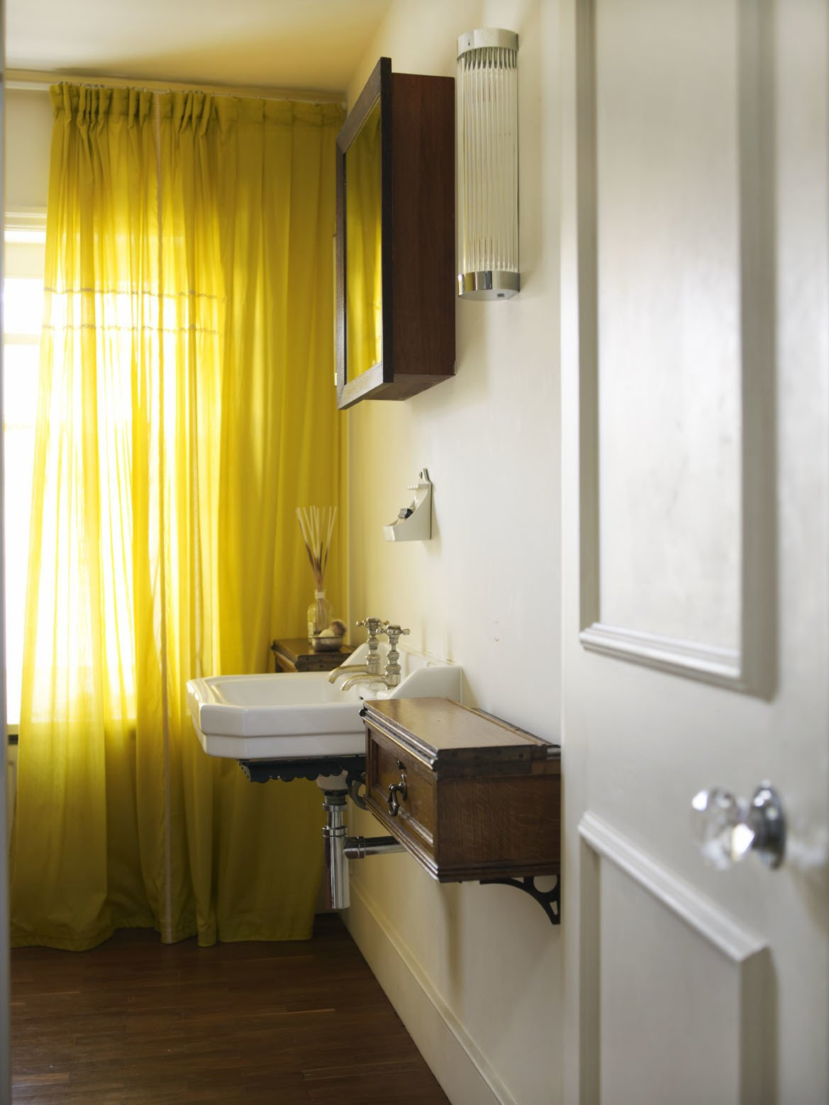 The cupboards of this bathroom are faced in panels of heavily aged leather, originally used on shelves in The British Library.