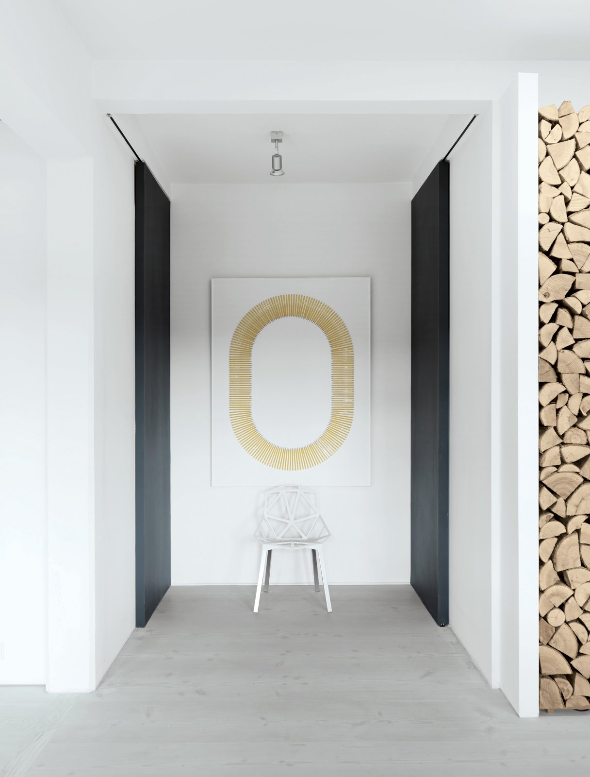 """Jensen's artwork hangs outside the family's bathroom. It was inspired by the industrial output—Viking pencils—of the former factory space. Putting his engineering studies to work, he created the art via a meticulous process that included making precise holes and a template of """"thousands"""" of pieces of paper. The stackable aluminum Chair_One is by   Konstantin Grcic for Magis.  Modern Danish Homes We Love by Aileen Kwun from Converted Loft Fit for a Modern Family in Copenhagen"""