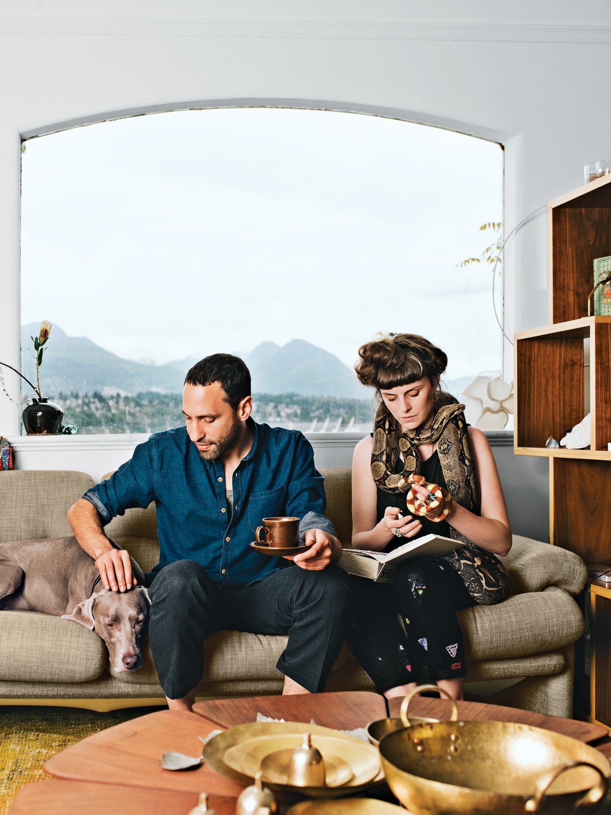 """In the living room of their Vancouver home, Omer Arbel and Aileen Bryant sit on a Coronado sofa by Afra and Tobia Scarpa for B&B Italia. They are joined by their Weimaraner, Bowie, boa constrictor, Picasso, and milk snake, Legs.  """"I have a casual approach to prototyping that involves our day-to-day life. I am always tinkering, and I have lots of transformers to run electricity through things, but Aileen lives with me now, so I have to be respectful. Before she moved in it was like a total madhouse; now I can't pour concrete in the kitchen. It is a collaboration in a sentimental sense. This work is my life, and the objects are my objects, but how they are arranged and the flow of each room are something we've created together here."""""""