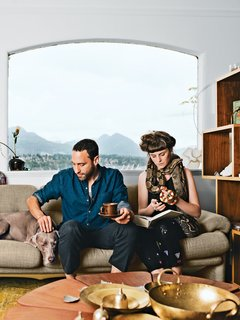 "45 Pets in Beautiful Modern Homes - Photo 5 of 45 - In the living room of their Vancouver home, Omer Arbel and Aileen Bryant sit on a Coronado sofa by Afra and Tobia Scarpa for B&B Italia. They are joined by their Weimaraner, Bowie, boa constrictor, Picasso, and milk snake, Legs.<br><br>""I have a casual approach to prototyping that involves our day-to-day life. I am always tinkering, and I have lots of transformers to run electricity through things, but Aileen lives with me now, so I have to be respectful. Before she moved in it was like a total madhouse; now I can't pour concrete in the kitchen. It is a collaboration in a sentimental sense. This work is my life, and the objects are my objects, but how they are arranged and the flow of each room are something we've created together here."""