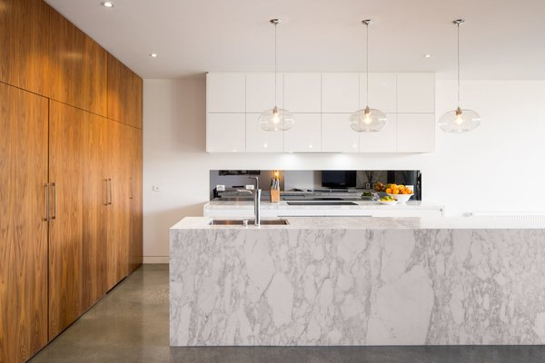 The entire living and dining space features tough polished concrete floors. The architects intentionally contrasted the darker concrete and veneered pantry against the neutral white walls and marble. This color play runs through the renovated areas.