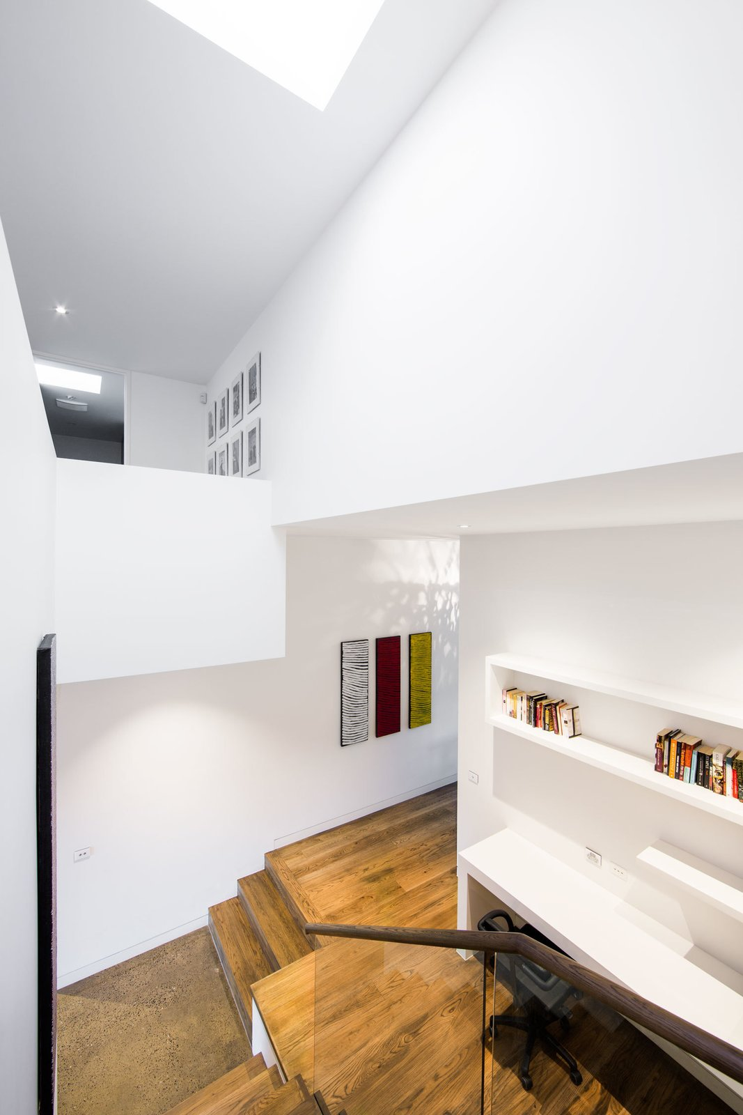 This double-height stairwell, just adjacent the kitchen, marks the transition from the historic building to the new renovation. A skylight pulls sunlight from above into the home office below. Tagged: Wood Tread, Wood Railing, Windows, and Skylight Window Type.  190+ Best Modern Staircase Ideas by Dwell from A Breezy Modern Addition Opens Up a Historic Melbourne Home