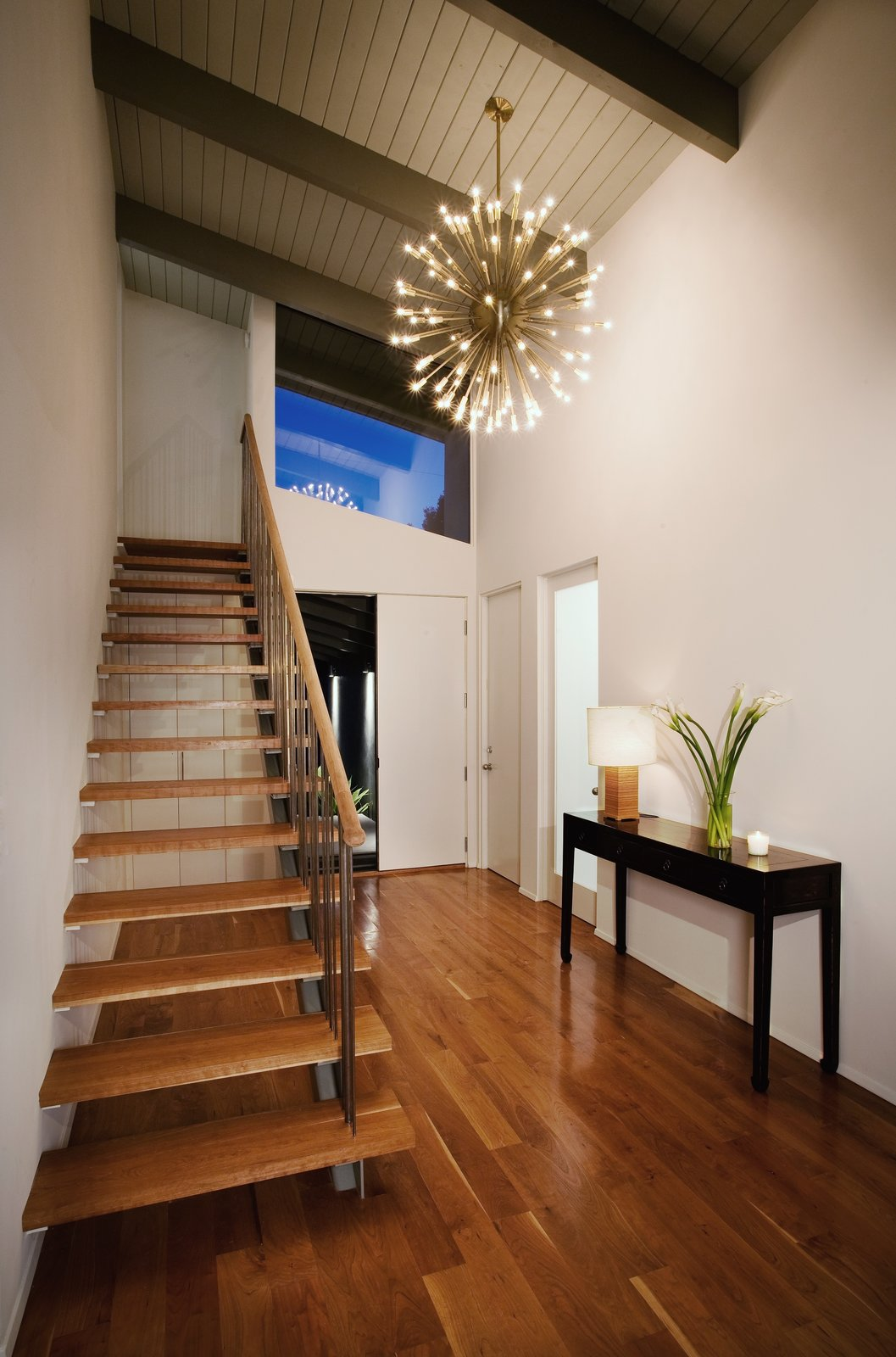 In the entryway, a brass Sputnik chandelier illuminates the airy American elm staircase.  190+ Best Modern Staircase Ideas by Dwell from A Renovation Elevates This Humble Ranch Among its Iconic Midcentury Neighbors