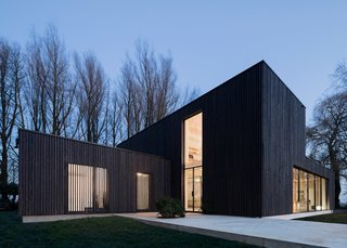 "This Blackened Timber House Triumphantly Emerges After a Fire - Photo 2 of 6 - ""We wanted the wood to appear as natural as possible, so leaving the larch untreated was the first choice,"" Bas explained. But the shape of the house would make the wood turn gray unevenly, so they blackened the larch. ""The clients were excited with the dark color as it helps the house blend into the trees. They didn't want the anything excessive or showy."" But blackened timber comes with its own challenges. Since it absorbs more heat, a larger air cavity was built behind the wood to keep it cool."