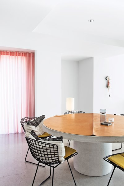 The couple has a fondness for mid-century designer Harry Bertoia, whose steel side chairs for Knoll ring the concrete dining table that they designed.