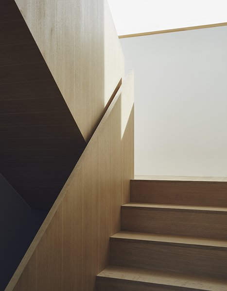 Wood is used throughout the home, as in a sculptural staircase designed by TACT.