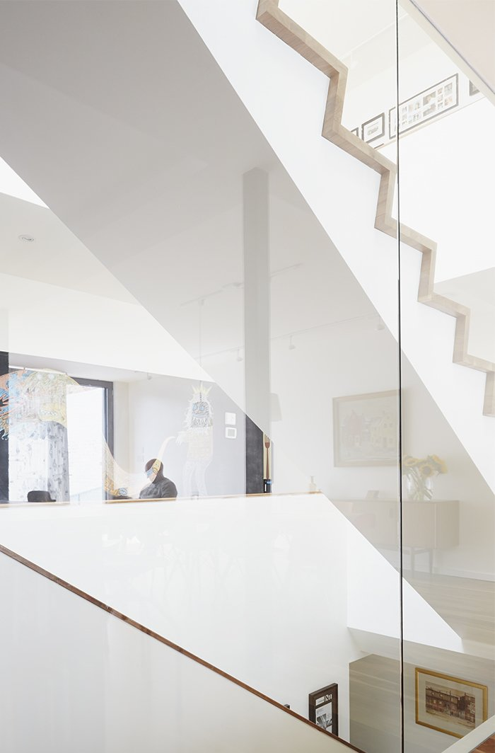 Large windows by Alumilex and an operable Velux skylight—with built-in rain sensor to automatically close it in case of unexpected showers—flood the home with light. A glass wall surrounding the staircase reflects a chalk mural by artist Tyson Bodnarchuk.