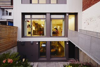 An Architectural Mishmash in Montreal Becomes a Long-Term Family Home - Photo 9 of 11 - At the rear of the house, exterior steel cladding by Vicwest updates the look of the facade, while a steel footbridge connects the garden to the main floor of the house