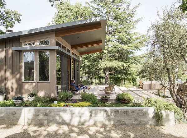 To install Charles Willson's prefab house, Stillwater Dwellings lifted the structure over an existing barn on the one-acre property. Willson, who is often on the road, wired the house with the latest in smart technology.