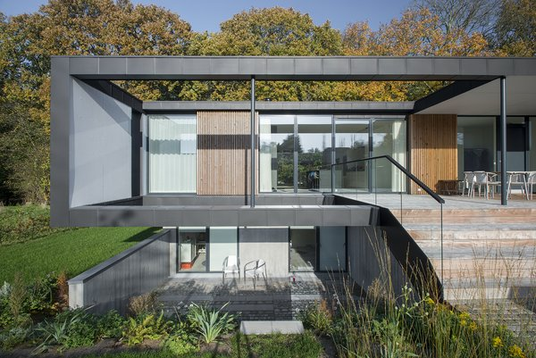 """Located in Aarhus, Denmark, Villa R is a minimalist, serene structure clad in zinc panels. """"The objective was to create a house that brings the forest inside through large glass panels—and create an ever-changing seasonal backdrop for the interior living spaces,"""" stated the architecture firm, C.F. Møller, of the 3,200-square-foot abode. Photo  of Villa R modern home"""