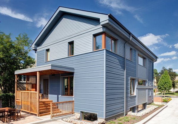The exterior was clad with LP SmartSide in alternating bands of textured and smooth siding and basement areaways are constructed of site-salvaged brick-filled gabions.  Photo by: Eric Hausman Photography