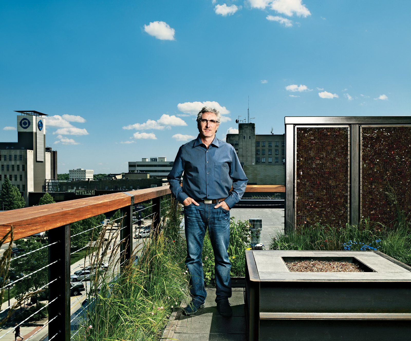 Fargo native son Doug Burgum stands on his rooftop deck. Landscape architect Brian Reinarts outfitted the space with local grasses and plants, LED-illuminated privacy screens, and a natural-gas fireplace.  Photo by: David Bowman