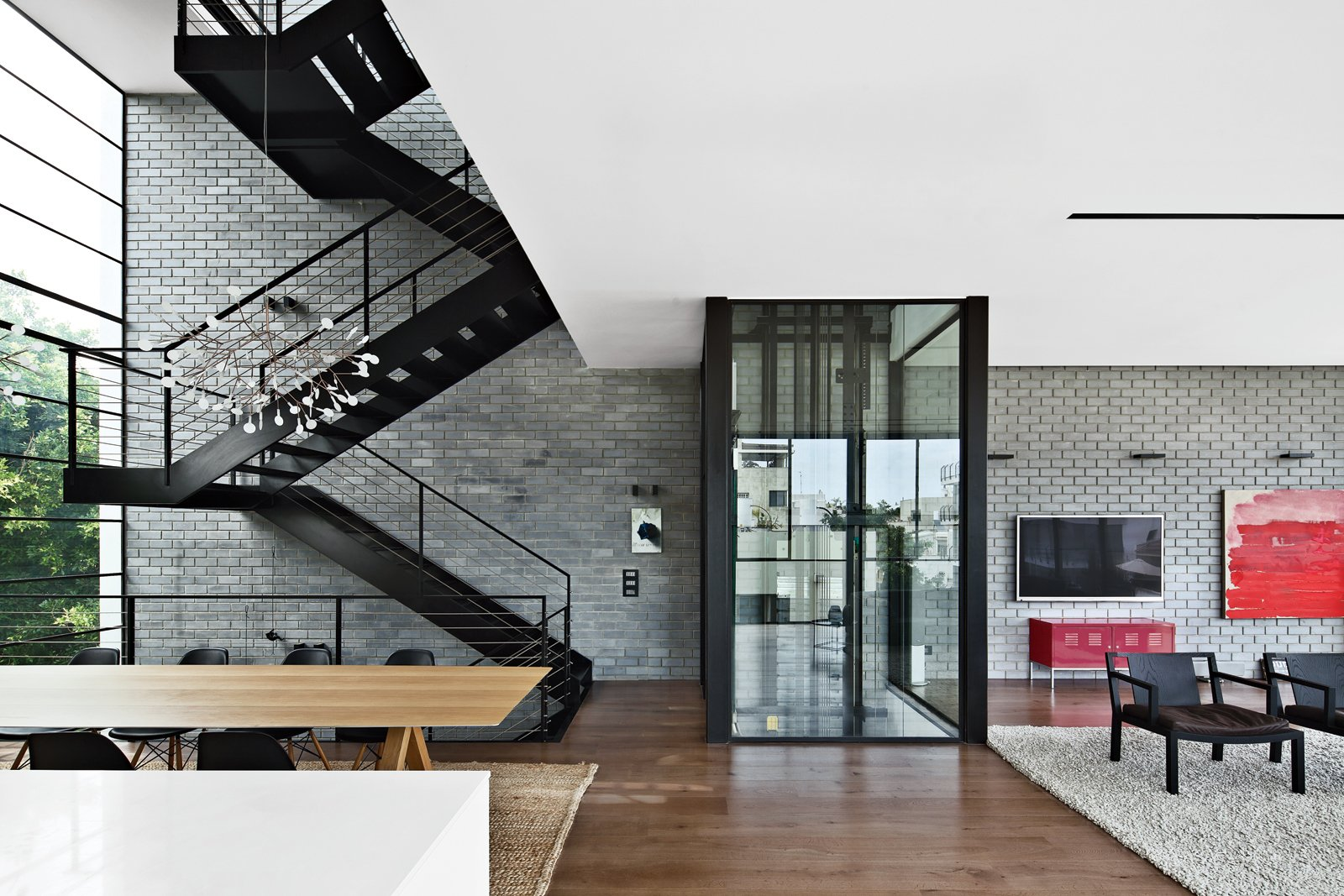 The residents use either the black steel staircase or a glassed-in elevator by Wittur to get around the house. Tagged: Living Room, Chair, Medium Hardwood Floor, and Rug Floor.  Inspiratie nieuw huis by Bram Kerssemakers from Modern High-Rise Town House in Tel Aviv