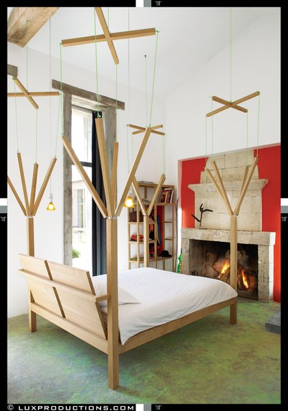 All of the beds in the house are playful custom one-off designs by Crasset, including the marionette-themed master bed, which a local carpenter fabricated from oak felled in the surrounding forest. The stone fireplace is original.