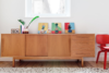 Keeping the white walls mostly bare also helped the apartment feel less cramped. Instead, a vintage Danish credenza offers a contained space on which to display small framed art works and other unique objects. Photo  of A Tiny Apartment Renovation for a Growing Family in Melbourne modern home