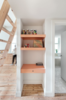 Whimsical salmon accents play favorably against the pine floors and plywood joinery. A ladder in the living room leads up to a mezzanine loft guest room while also creating a compact work nook below. Photo  of A Tiny Apartment Renovation for a Growing Family in Melbourne modern home