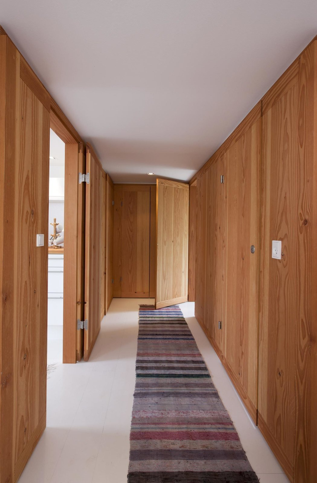 Douglas fir lines the walls of the entryway. A narrow striped rug adds texture to the white-painted wooden floor from Dinesen. Tagged: Hallway.  Hallways That Impress by Ethan Lance from A Thatched Cottage in Denmark with a Modern, Space-Saving Interior