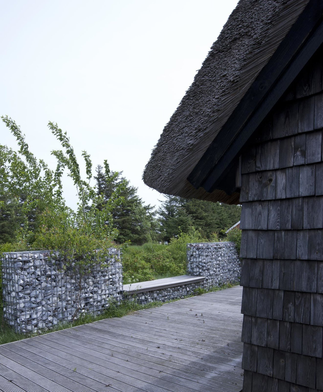"""A modern stone fence made of galvanized steel mesh filled with stones surrounds the house. """"We got the stones from the local stonecutter—they use the stones washed up on the beach, not the stones from the fields,"""" Lassen explains."""