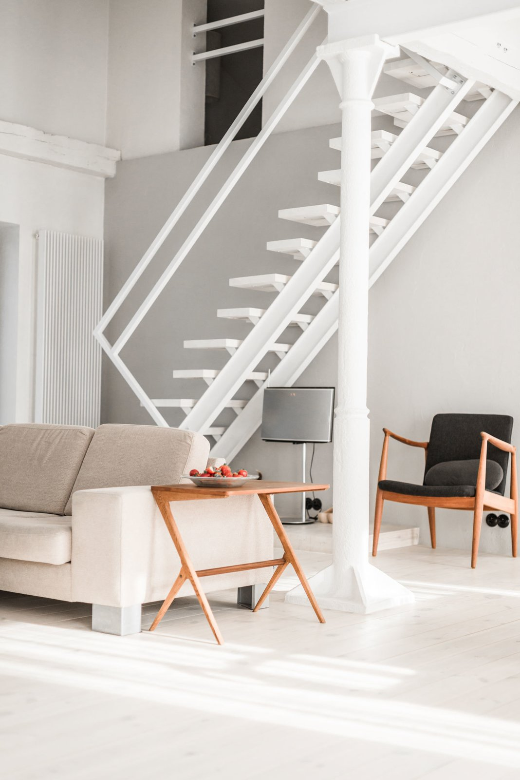 "The designer took his inspiration for the minimal staircase from traditional Polish ""duck stairs."" Since they're narrow, they're ideal for smaller spaces. The couch was purchased from BoConcept. Tagged: Living Room, Sofa, and Chair.  Best Photos from A Run-Down Farmhouse Becomes a Sleek Modern Retreat"