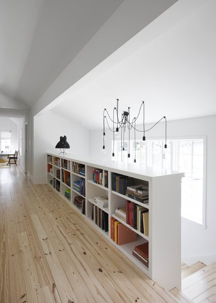 "Flournoy's favorite aspect of the design is that ""every space in the house is used and appreciated."" This light-filled hallway overlooking the staircase connects the home's two bedrooms to an upstairs living space, and provides the ideal spot for another bookcase. Flournoy and his partner found the hall chandelier, along with the salvaged mill table that they repurposed as their kitchen island, on a trip to Chicago."