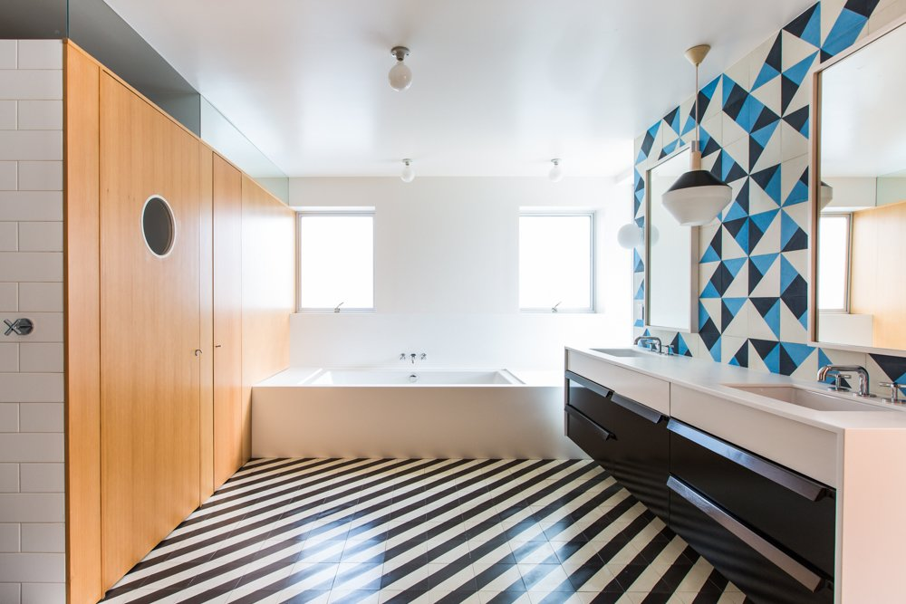 Architect Barbara Bestor added a striped floor of Santander Granada Tile, Douglas Fir cladding, and Granada Serengeti tile flipped to create a one-of-a-kind pattern on the wall.  Photo 13 of 20 in 20 Bathrooms With Transformative Tiles from A Bright, Geometric Bathroom Renovation in Los Angeles