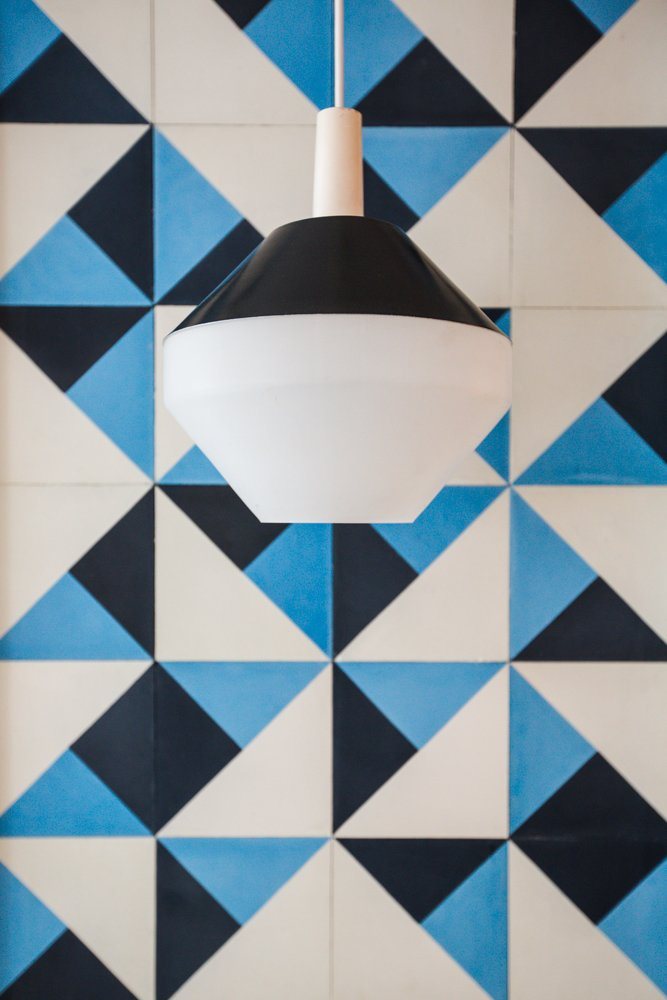The pendant, sourced from Amsterdam Modern, is made from Black spun aluminum and vintage Pilastro Diamond milk glass.  Pattern by Lara Deam from A Bright, Geometric Bathroom Renovation in Los Angeles