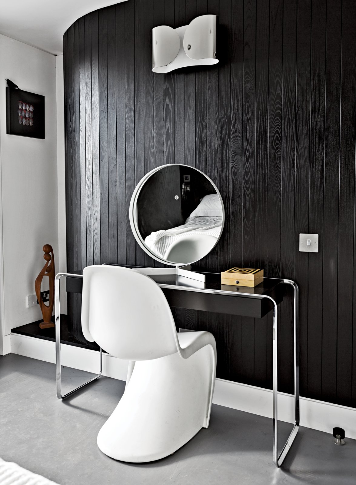 "Near the room's curving wall, a Verner Panton chair joins a K2 B console table by Tecta, topped by a vintage mirror by Robert Welch. The wall light is from Flos. ""If I had more space, I'd just fill it with more stuff,"" says Pearce. Tagged: Bedroom, Wall Lighting, and Concrete Floor.  Photo 3 of 7 in An Elevated Deckhouse in England"