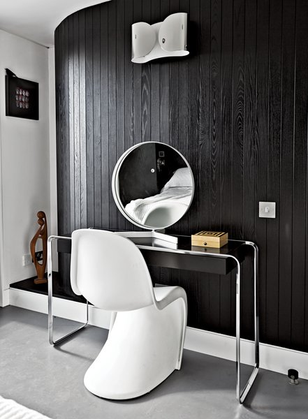 "Near the room's curving wall, a Verner Panton chair joins a K2 B console table by Tecta, topped by a vintage mirror by Robert Welch. The wall light is from Flos. ""If I had more space, I'd just fill it with more stuff,"" says Pearce."