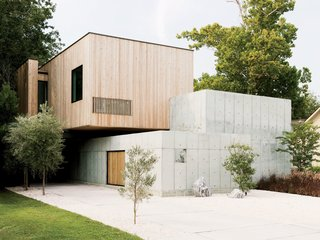 A Texas Couple Builds Their Cast-In-Place Concrete Dream Home - Photo 3 of 17 - Designers Christopher Robertson and Vivi Nguyen-Robertson conceived their house as an unfolding sequence of simple geometric forms: a low concrete wall, a concrete cube, and a box clad in Siberian larch.
