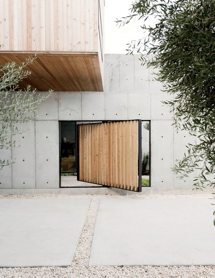 A pivoting door, also made of larch, provides a shortcut to enter the structure as an alternative to the main courtyard entrance. Tagged: Doors, Wood, Exterior, and Swing Door Type.  Photo 1 of 17 in A Texas Couple Builds Their Cast-In-Place Concrete Dream Home