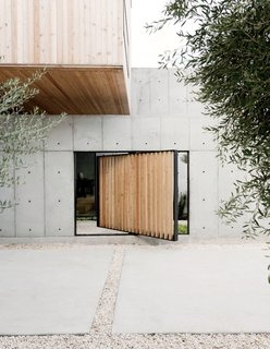 A Texas Couple Builds Their Cast-In-Place Concrete Dream Home - Photo 1 of 17 - A pivoting door, also made of larch, provides a shortcut to enter the structure as an alternative to the main courtyard entrance.