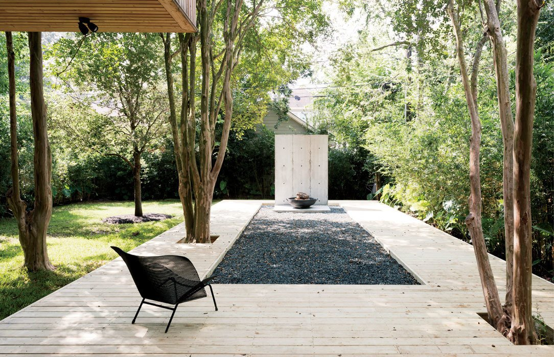 The metal Grillage chair on the deck is by François Azambourg for Ligne Roset. Tagged: Outdoor, Large Patio, Porch, Deck, Wood Patio, Porch, Deck, and Grass.  Photo 4 of 17 in A Texas Couple Builds Their Cast-In-Place Concrete Dream Home