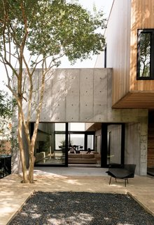Sliding doors from Western Window Systems connect the living room and the deck, which is made of pressure-treated pine planks surrounding a black gravel pit.