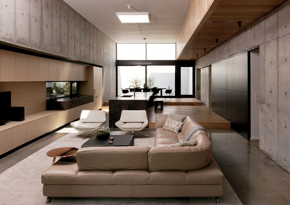 The living room features a sofa from Roche Bobois, Metropolitan armchairs by Jeffrey Bernett for B&B Italia, and a Good Morning table in copper and Anytime table in anthracite frosted glass from Ligne Roset. The rug is by Tissage. Tagged: Living Room, Sectional, Chair, and Ceiling Lighting.  Photo 6 of 17 in A Texas Couple Builds Their Cast-In-Place Concrete Dream Home