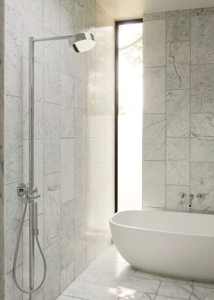 The master bath is clad in Bianco Venatino marble. The tub is by ADM; the showerhead is by Hansgrohe.