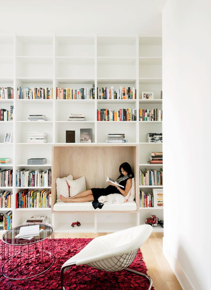 Awaiting the birth of the couple's son, Vivi relaxes in a built-in reading nook in the library. Tagged: Living Room, Coffee Tables, Chair, Bench, Light Hardwood Floor, and Rug Floor.  Photo 9 of 17 in A Texas Couple Builds Their Cast-In-Place Concrete Dream Home