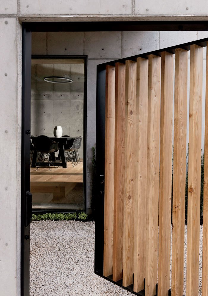 """We talked about creating a sense of mystery when [guests] walked in from the street,"" says Christopher. A gate swings open on a steel bar-stock frame to reveal a courtyard and the dining room beyond. Tagged: Doors, Exterior, Wood, and Swing Door Type.  Photo 13 of 17 in A Texas Couple Builds Their Cast-In-Place Concrete Dream Home"