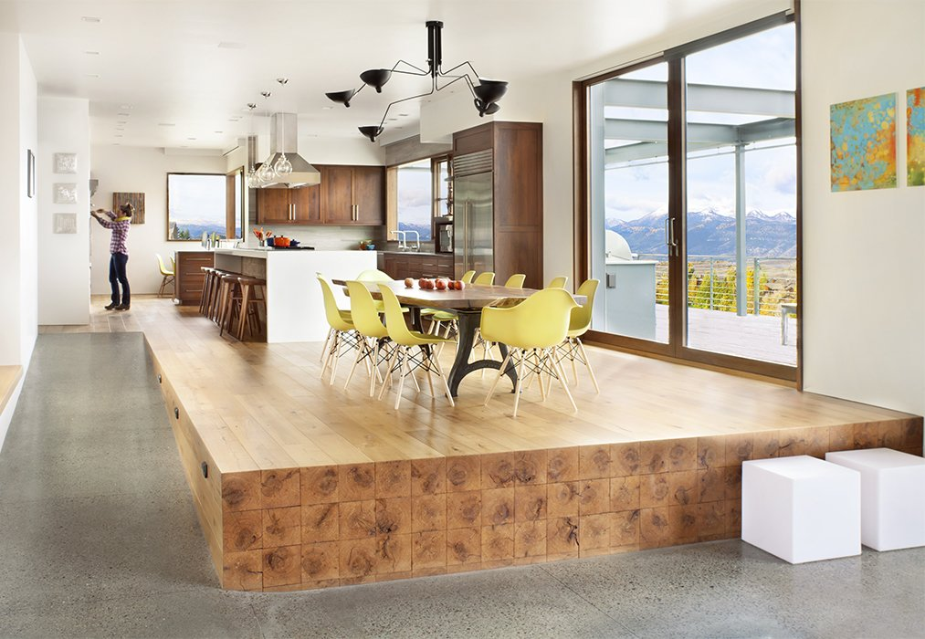 Beams extending from the kitchen floor give the impression of an oversize butcher-block stage for a custom walnut-slab table and a dozen Molded Plastic chairs by Charles and Ray Eames for Herman Miller. A Custom, LED-Lit Slide Twists Through This Family-Friendly Vacation Home - Photo 4 of 11
