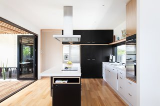 A Modular Beach Home in Australia Allows One Family to Keep an Eye on the Surf - Photo 7 of 8 - In the kitchen, an island countertop serves as a mixed-use area for cooking, storage, and seating for up to five people. The room opens up to an outdoor dining area.