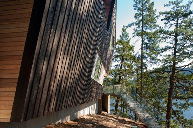 """The house cantilevers out over the landscape for unimpeded views. """"It's canted wall defines the main entrance and creates a covered space for unpacking and packing—a familiar family ritual,"""" Howat says. Tagged: Exterior, Cabin Building Type, and Wood Siding Material.  Best Photos from Gambier Retreat"""