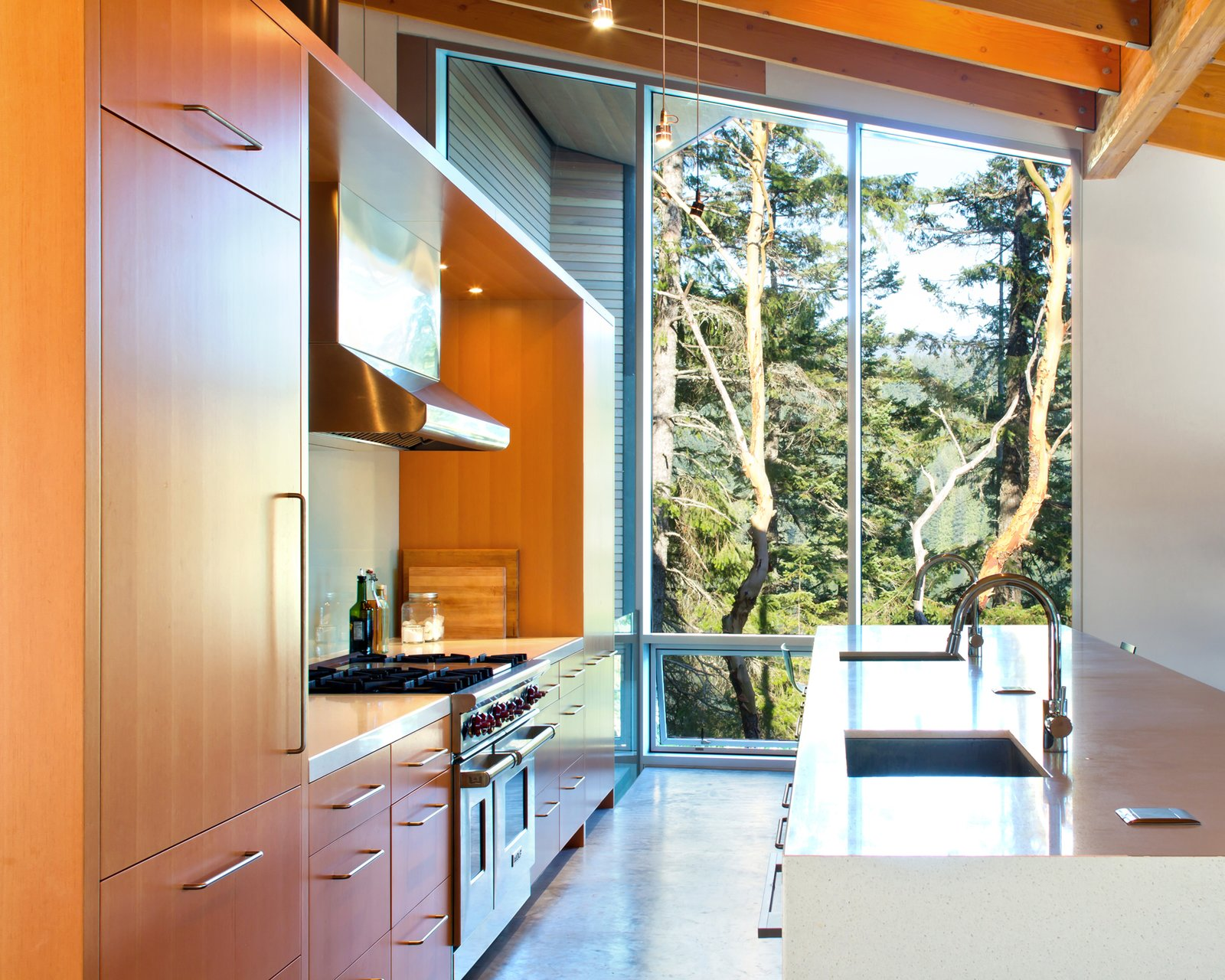 Light streams in through the kitchen from massive, floor-to-ceiling windows that offer peaceful views of the outside foliage. Tagged: Kitchen and Wood Cabinet.  Best Photos from Gambier Retreat