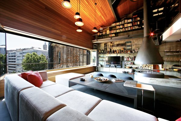 "The team's design philosophy was ""not to have too many ideas,"" and instead focus on a few key aesthetic moves that would be carried through the entire space. The lower living level features a full-wall storage system and statement hearth on a concrete platform. Sectional seating offers sweeping city views of Karakoy, including an old Armenian church and Galata Tower."