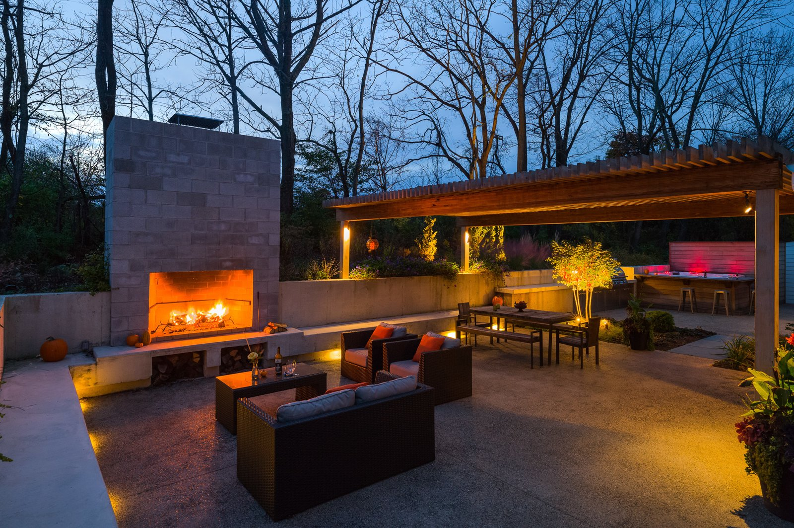 """A small wooden deck originally anchored the backyard, which has since been transformed into a larger social area. """"We wanted something that was sunken into the earth that would feel like you're enveloped by the surroundings,"""" Michael says. In order to achieve this, he installed a concrete retaining wall that's level with the soil above it, so foliage will gradually grow into the living space. This feature creates an almost ruin-like feeling and a direct connection to the surrounding landscaping.  Photo 7 of 8 in A Loving Renovation Updates a Rustic Family Home with Reclaimed Materials"""