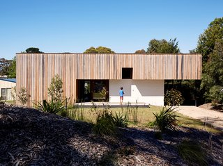 Simplicity Rules at this Family Beach House Designed to Double as a Rental - Photo 1 of 11 - Rachel Nolan and Steven Farrell's weekend house is located a couple of blocks from the beach on Australia's Mornington Peninsula. Built with passive principles in mind, the low-slung structure features double-thick brick walls for thermal massing. The vertical wood cladding is unfinished spotted gum, a local timber.