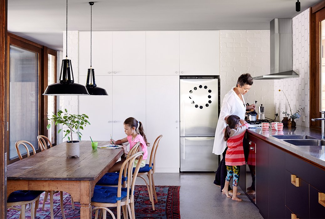 A no-fuss sensibility permeates the house. For example, the utilitarian kitchen has laminate cabinets, a stainless-steel countertop, and a Miele stove and dishwasher. The refrigerator is by Fisher & Paykel. No. 18 chairs from Thonet and a reclaimed-hardwood table are stationed atop a vintage Persian soumak rug from Turkey. Tagged: Kitchen, Concrete Floor, and Concrete Counter.  Photo 2 of 11 in Simplicity Rules at this Family Beach House Designed to Double as a Rental