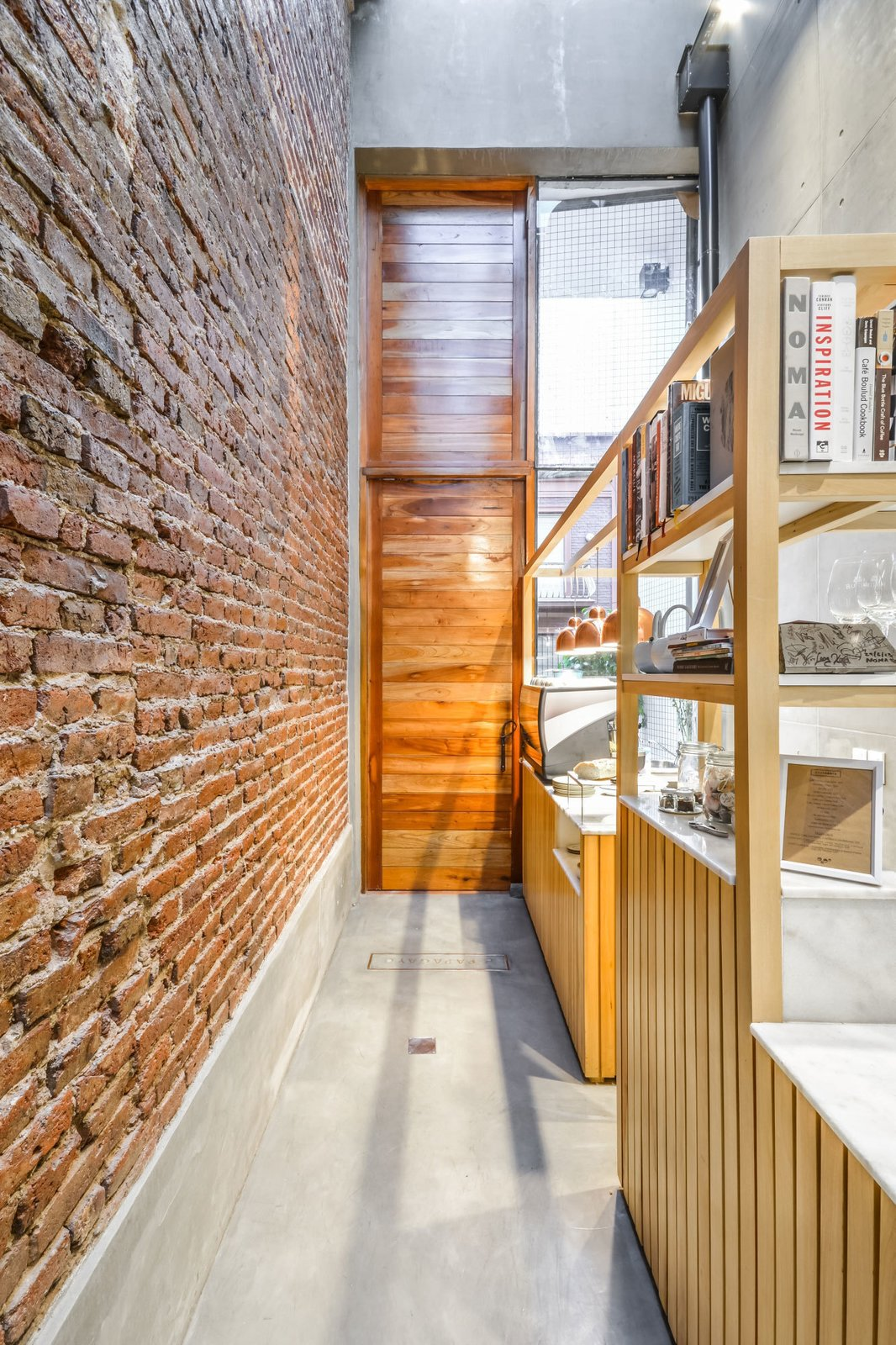 The space is also adorned with timber cladding, as seen on the entry door.  Photo 2 of 11 in 10 Fantastically Sleek Foyer Designs from This Amazingly Tiny Restaurant in an Alley Is Under 8 Feet Wide