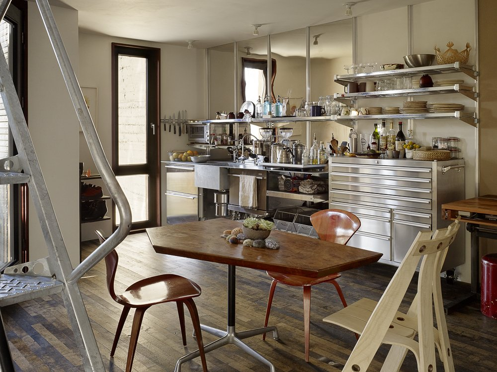 Outfitted with shelves by EZ Shelving and a generic tool chest, the kitchen's galvanized steel integrated counter and sink was designed by Baker and fabricated by DeFauw Design + Fabrication. A vintage pair of Norman Cherner's Plycraft chairs and an A Chair by sustainable furniture-maker David Colwell surround a table by Pacassa Studios, which mounted a custom top on a Herman Miller Eames base. All appliances are electric, including heat-radiating panels, a combo washer-dryer unit, and an induction stove.